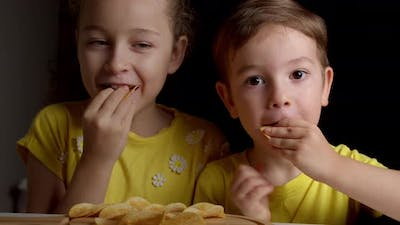 Cute Little Funny Kids Boy and Girl Eat Potato Chips Kids Take Chips and Have Fun Kids Eat at the