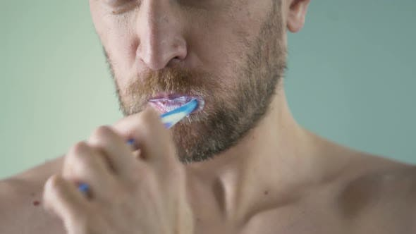 Thumbnail for Bearded Middle-Aged Man Carefully Brushing His Teeth Looking in Mirror, Close-Up