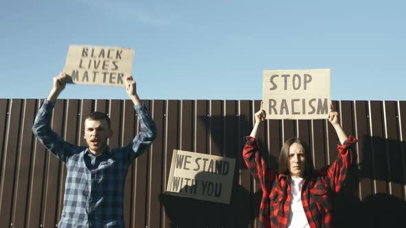 Thumbnail for People chanting with posters BLACK LIVES MATTER and STOP RACISM against brown wall