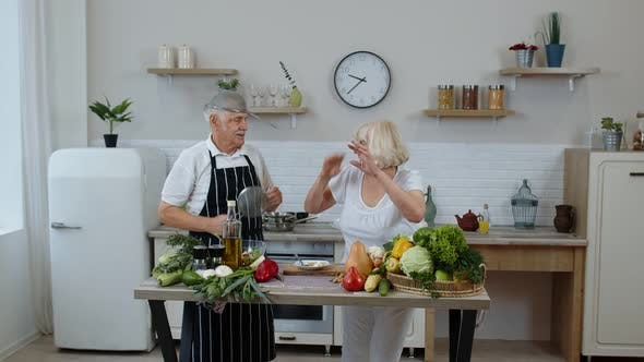 Thumbnail for Senior Woman and Man Making a Funny Dance with Strainers. Dancing While Cooking Together in Kitchen