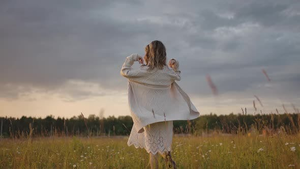 Thumbnail for Female Putting on Long Warm Jacket in Meadow