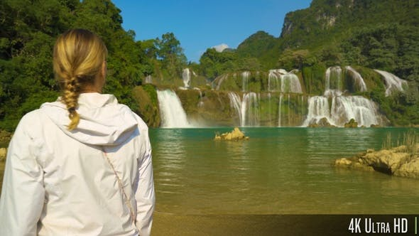 Thumbnail for 4K Female Tourist Walking in Front of the Ban Gioc Waterfall Vietnam