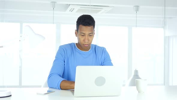 Thumbnail for Afro-amerikanischer Mann arbeitet auf Laptop im Büro