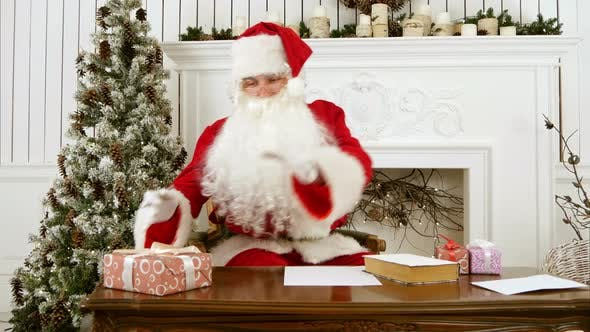 Cover Image for Santa Claus Sitting at the Table in His Christmas Workshop Signing Presents for Children