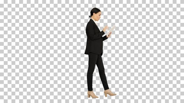 Businesswoman using a tablet pad while walking, Alpha Channel