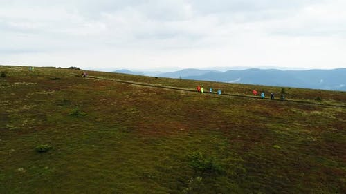 Tourists in Raincoats Go on a Mountain Range