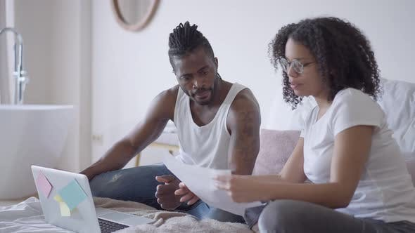 Concentrated African American Man Listening to Intelligent Young Woman Explaining Graphs