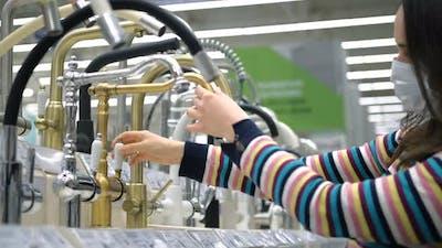 Woman Choosing a Water Tap in Plumbing Store