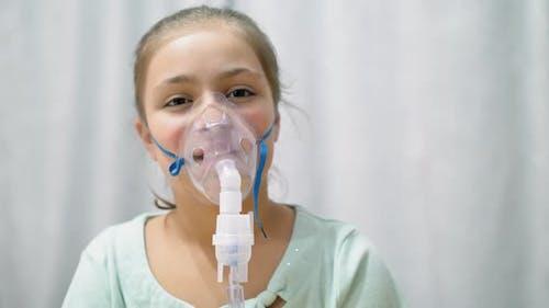Teen Girl Inhaling Through Inhaler Mask