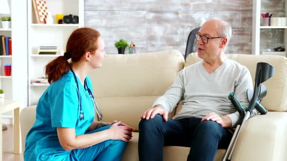 Thumbnail for Female Nurse Talking and Taking Care of Old Disabled Man Sitting on the Sofa