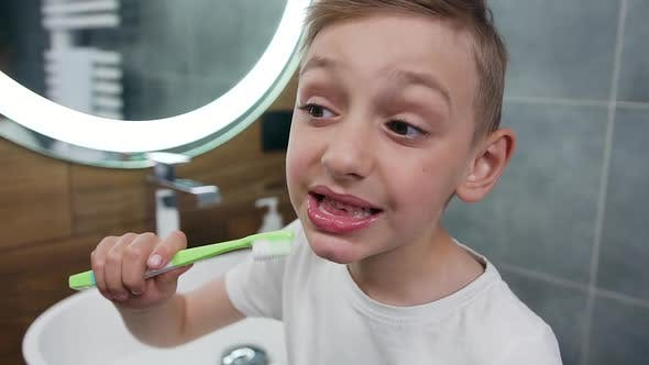 Thumbnail for 10-Aged Boy Cleaning His Teeth Using Toothbrush and Toothpaste, Standing Near the Bathroom Mirror