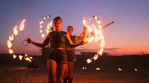 Professionelle Künstler zeigen eine Feuershow bei einem Sommerfestival auf dem Sand in Zeitlupe