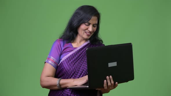 Thumbnail for Mature Happy Beautiful Indian Woman Smiling While Using Laptop