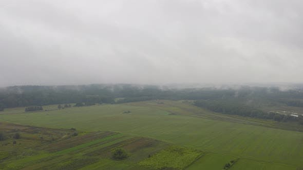 Thumbnail for Aerial Hyperlapse, Top View Drone Flies Through Rain Clouds Rolling Over Green Forest and Field
