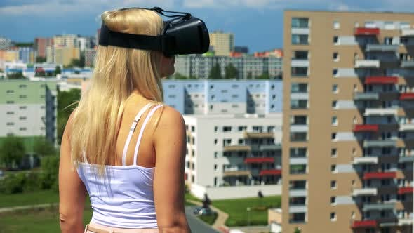 Thumbnail for Young Attractive Blond Woman Uses Virtual Reality Glasses - Buildings in the Background
