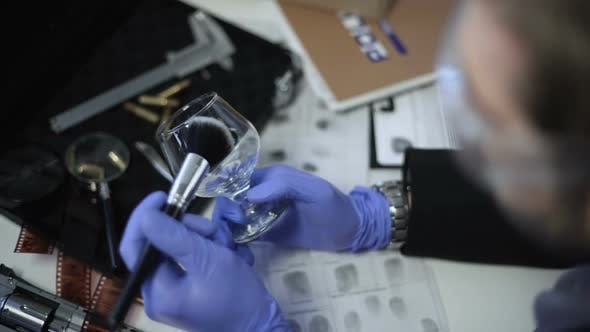 Thumbnail for Detective in Gloves Lifting Fingerprints on Wine Glass, Using Brush and Powder