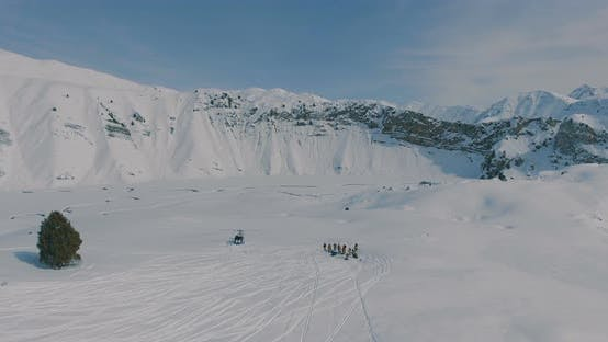 Thumbnail for Aerial overflight over a helicopter, a group of skiers and snowboarders in the winter mountains