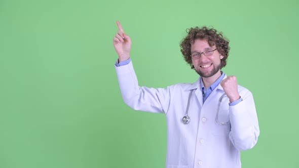 Cover Image for Happy Young Bearded Man Doctor Pointing Up and Getting Good News