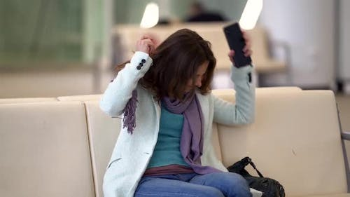Angry Woman Is Waiting Flight in Airport, Sitting in Waiting Area, Flight Delay or Canceled