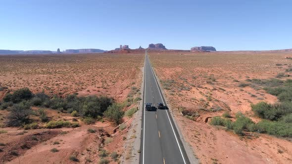Thumbnail for Drone Follows Two Cars Driving Along Beautiful Highway Road Monuments Valley