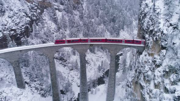 Thumbnail for Landwasser Viaduct with Railway and Train in Winter. Snowing. Swiss Alps. Switzerland. Aerial View