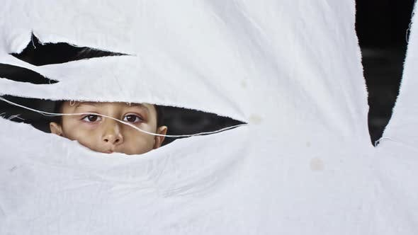 Thumbnail for Refugee Boy Looking through Torn Cloth