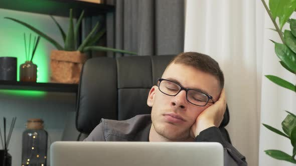 Thumbnail for Sleepy tired male employee is sleeping at workplace near laptop.