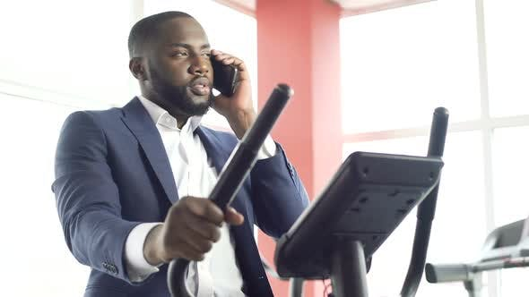 Thumbnail for Serious Male in Suit Exercising on Stationary Bike and Talking on Cellphone