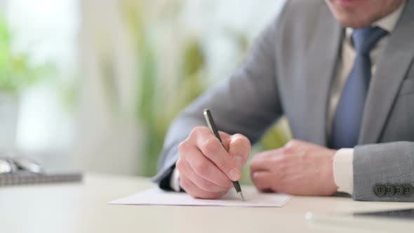 Close Up of Businessman Writing on Paper with Pen