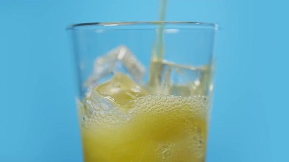 Thumbnail for Pouring Orange Fizzy Drink. Glass Full of Cold Sparkling Cocktail with Lot of Ice Cubes on Blue BG
