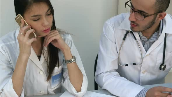 Thumbnail for Female Assistant Talking on the Phone Asking Male Doctor for Advice