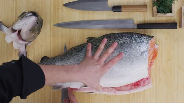 Thumbnail for Overhead shot of chef cutting up large Salmon fish