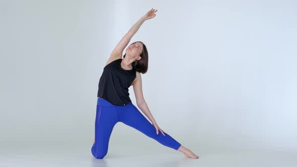Fit Woman in Sportswear Practicing Yoga Gate Pose at Home