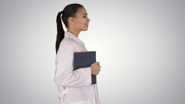 Thumbnail for Happy smiling female doctor walking holding notebooks