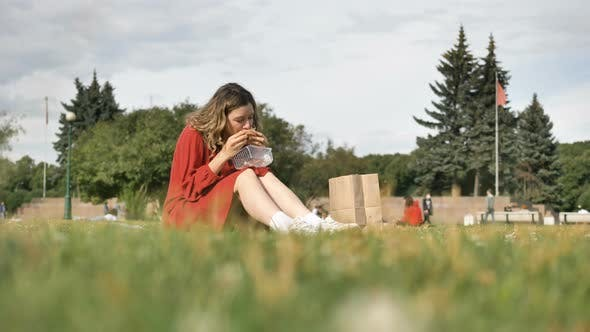 Thumbnail for Woman in Red Dress Eats Lunch Sitting on Grass in City Park