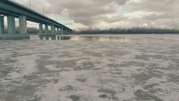 Picturesque Wide Frozen River Under Grey Bridge Aerial View