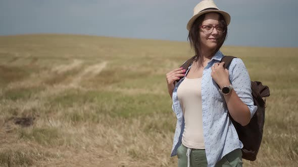 Thumbnail for Woman Traveler with a Backpack Walks on a Hill