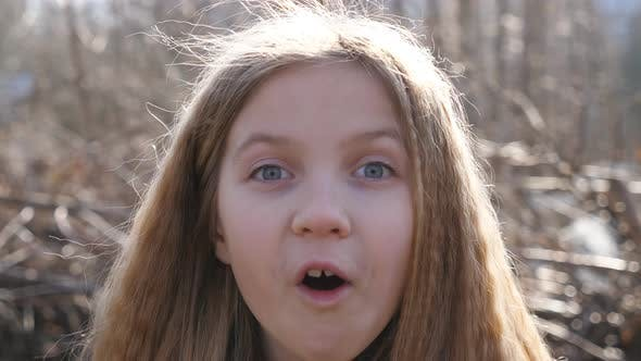 Thumbnail for Happy Little Blonde Girl Looking Into Camera with Wow Expression Outdoor. Portrait of Beautiful