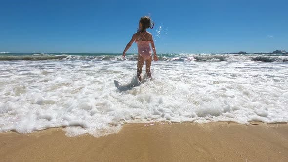 Thumbnail for Happy Little Girl Wearing Pink Swimsuit Jumping and Playing with See Waves on the Beach