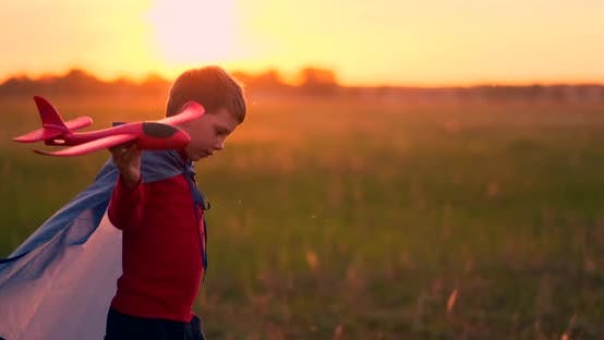Thumbnail for Young Boy Pilot and Runs in Field at Sunset and Playing with Plane Dreaming