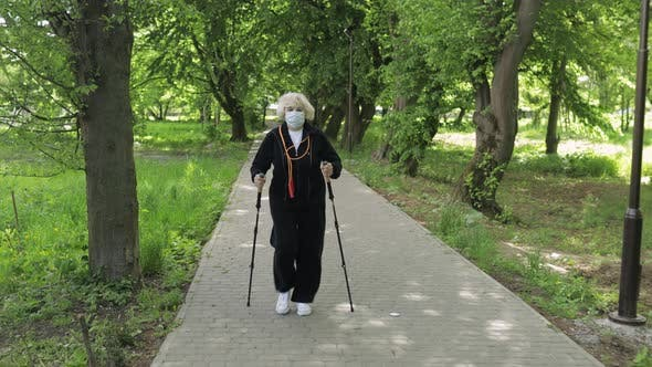 Active Senior Old Woman in Mask Training Nordic Walking in Park at Quarantine