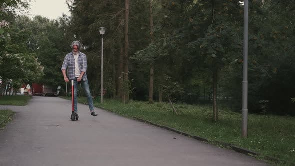 Thumbnail for Stylish Senior Man Riding a Scoother on the Road in a Park