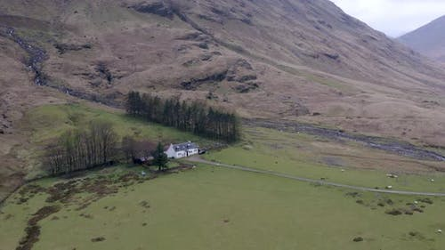 The Glencoe Valley and a Small House Surrounded by Mountains in the Highlands