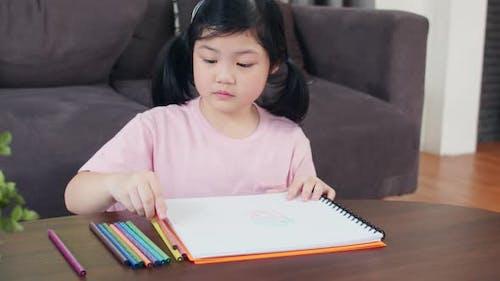 Junge asiatische Mädchen zeichnen sich entspannen Rest Spaß glücklich Zeichnen Cartoon im Skizzenbuch.