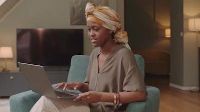 Smiling Black Woman Typing on Laptop