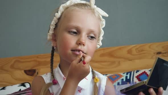 Little cute girl paints her lips