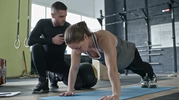 Thumbnail for Cross Training Instructor Supporting Woman while She Doing Push-Ups