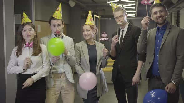 Thumbnail for Five Positive Caucasian Office Workers in Party Hats Looking at Camera and Smiling in Open Space