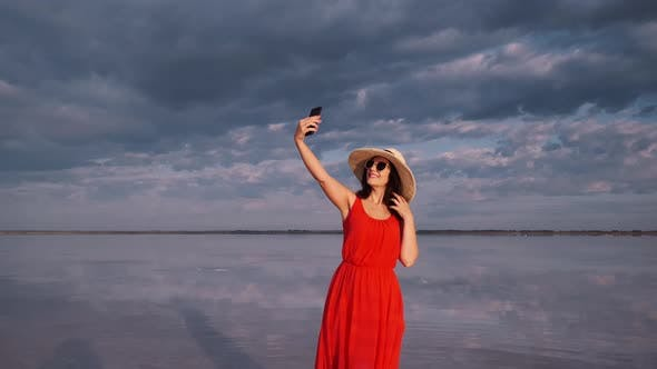 Thumbnail for Young Woman Tourist Takes a Selfie in a Beautiful Unusual Place. Girl in a Red Dress, Hat and