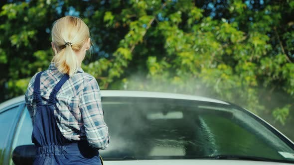 Rear View of A Woman Washing My Car in the Backyard of Her House on the Background of the Doors